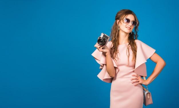 Jonge stijlvolle sexy vrouw in roze luxe jurk zomer modetrend, chique stijl, zonnebril, blauwe studio achtergrond, fotograferen op vintage camera