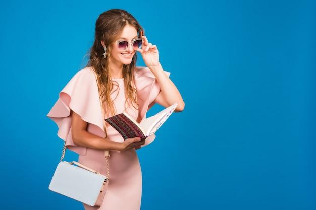 Jonge stijlvolle sexy vrouw in roze luxe jurk zomer modetrend, chique stijl, zonnebril, blauwe studio achtergrond, mode bloger