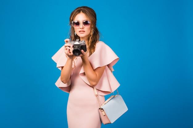 Jonge stijlvolle sexy vrouw in roze luxe jurk zomer modetrend, chique stijl, zonnebril, fotograferen op vintage camera