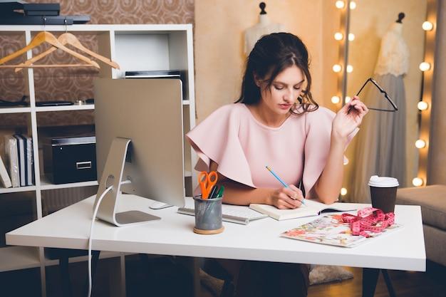 Jonge stijlvolle sexy vrouw in roze luxe jurk zomer trend, chique stijl, modeontwerper werken op kantoor op computer