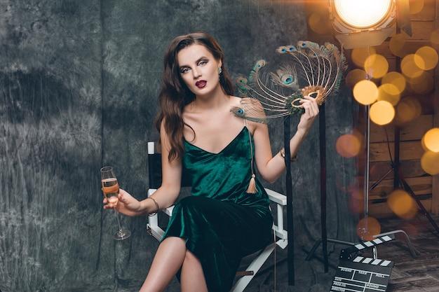Jonge stijlvolle sexy vrouw zittend in stoel op bioscoop backstage