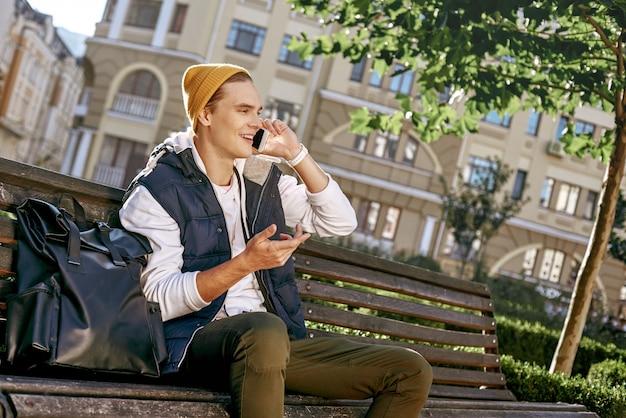 Jonge stijlvolle toeristenblogger gebruikt telefoon op de bankclose-up