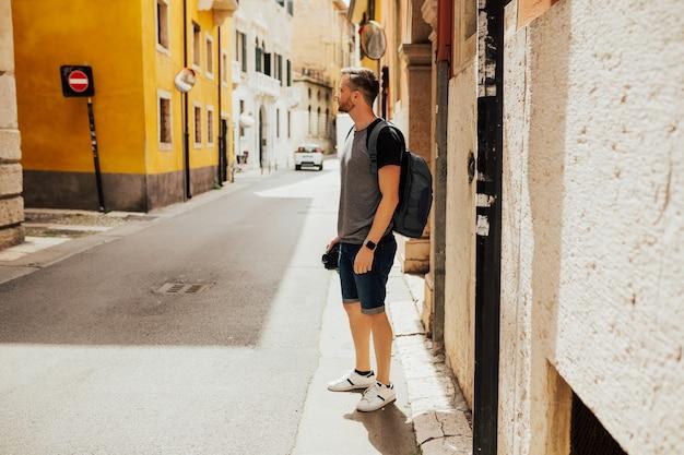 Jonge stijlvolle toeristische man met rugzak de straten van verona, italië verkennen