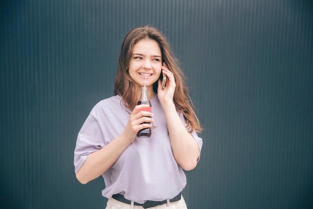 Jonge stijlvolle trendy vrouw geïsoleerd over grijs blauwe achtergrond. meisje praten over de telefoon en frisdrank drinken donker bruisend water uit glazen fles door middel van plastic rietje.