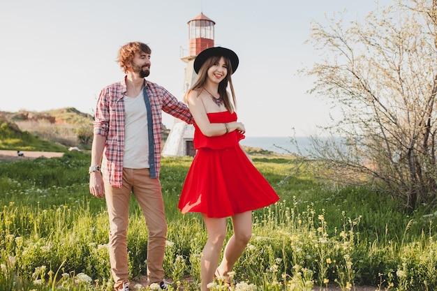 Jonge stijlvolle verliefde paar dansen op platteland, indie hipster bohemien stijl, weekendvakantie, zomer outfit, rode jurk, groen gras, hand in hand
