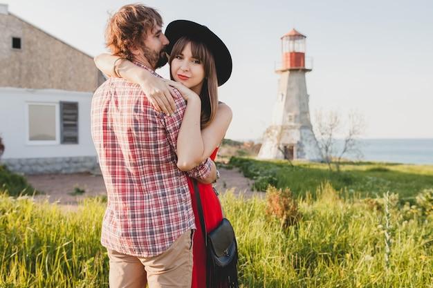 Jonge stijlvolle verliefde paar omarmen op platteland, indie hipster bohemien stijl, weekendvakantie, zomer outfit, rode jurk, groen gras, hand in hand