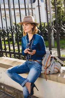 Jonge stijlvolle vrij gelukkige vrouw glimlachend en houden telefoon, gekleed in denim overhemd en spijkerbroek