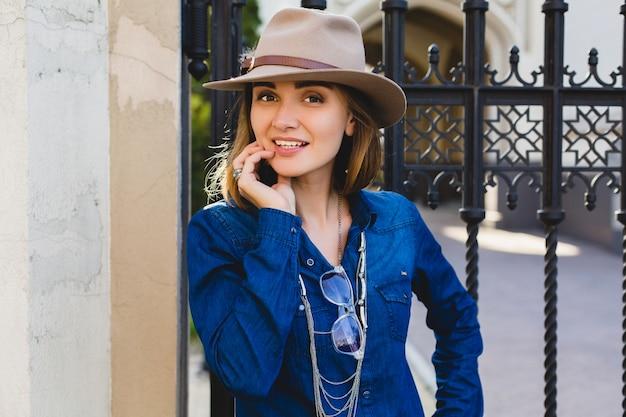 Jonge stijlvolle vrij gelukkige vrouw glimlachend en poseren, gekleed in denim overhemd