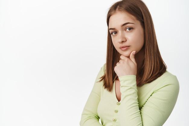Jonge stijlvolle vrouw denkt, kijkt attent naar voren, glimlacht en raakt de kin aan, denkt na, luistert met belangstelling, staat tegen de witte muur.