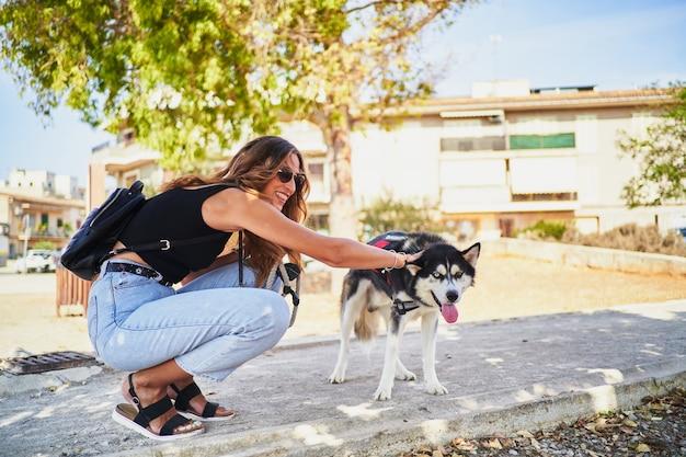 Jonge stijlvolle vrouw die haar siberische husky meeneemt voor een ritje in het park