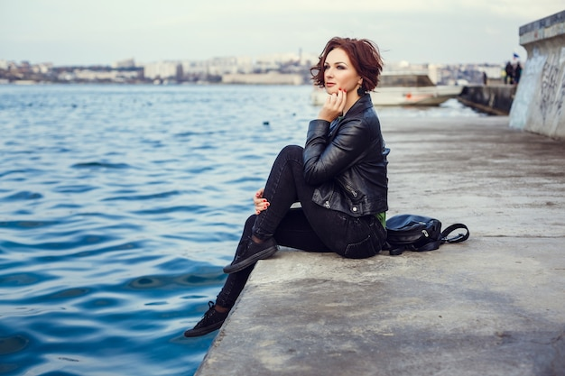 Jonge stijlvolle vrouw dragen zwarte jas, broek en handtas wandelen in de stad straat in herfst seizoen. wintermode, elegante look. plus size model.