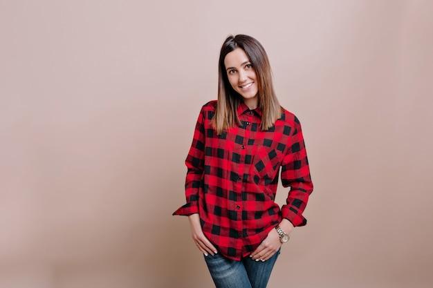Jonge stijlvolle vrouw gekleed geruit overhemd en spijkerbroek vormt op de geïsoleerde muur met charmante glimlach en gelukkige emoties