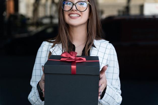 Jonge stijlvolle vrouw handen cadeau. gelukkige jonge vrouw houdt geschenkdoos vast en glimlacht. zwarte geschenkdoos met rode strik.
