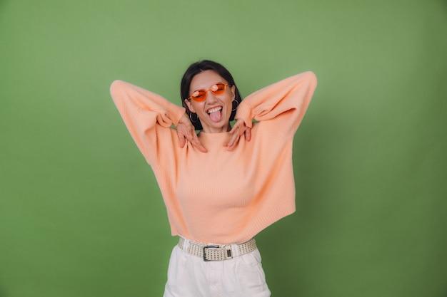 Jonge stijlvolle vrouw in casual perzik trui en oranje bril geïsoleerd op groene olijf muur gelukkig positief grappig springen rond kopie ruimte