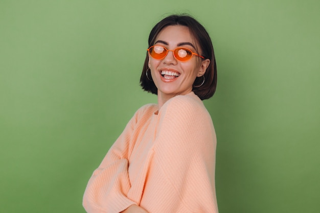 Jonge stijlvolle vrouw in casual perzik trui en oranje bril geïsoleerd op groene olijfmuur gelukkig positief lachend lach rond kopie ruimte