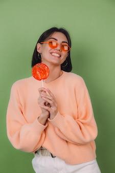 Jonge stijlvolle vrouw in casual perzik trui en oranje bril geïsoleerd op groene olijfmuur met oranje lolly positieve glimlach kopie ruimte