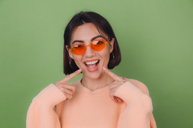Jonge stijlvolle vrouw in casual perzik trui en oranje bril geïsoleerd op groene olijfmuur positief lachend wijzend op witte tanden met wijsvinger kopie ruimte
