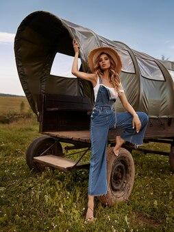 Jonge stijlvolle vrouw in denim overall poseren in de buurt van oude houten koets in het veld