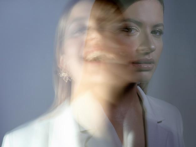 Jonge stijlvolle vrouw in een witte jas vervormingen van het gezicht van de modellen