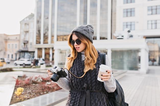 Jonge stijlvolle vrouw in warme wollen trui, moderne zonnebril en gebreide muts wandelen met koffie te gaan in het stadscentrum. reizen met rugzak, toerist met camera, opgewekte sfeer.