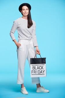 Jonge stijlvolle vrouw in witte broek, sneakers en gestreepte pullover poseren met boodschappentas op blauwe muur geïsoleerd