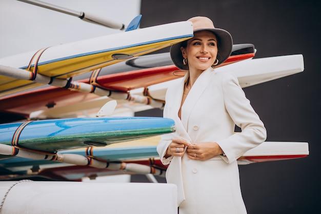 Jonge stijlvolle vrouw in witte jas reizen