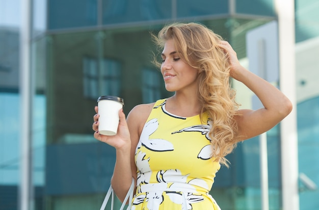 Jonge stijlvolle vrouw koffie drinken te gaan in een stad straat
