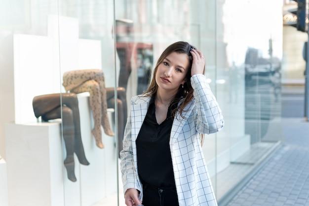 Jonge stijlvolle vrouw loopt door het winkelcentrum. portret van meisje op de achtergrond van het venstergeval.