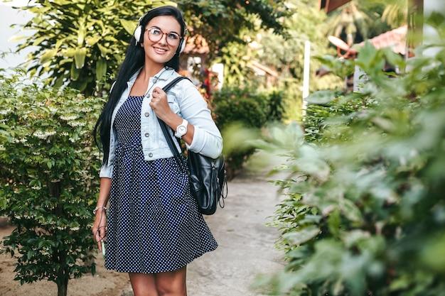 Jonge stijlvolle vrouw lopen met smartphone, luisteren naar muziek op de koptelefoon, zomervakantie