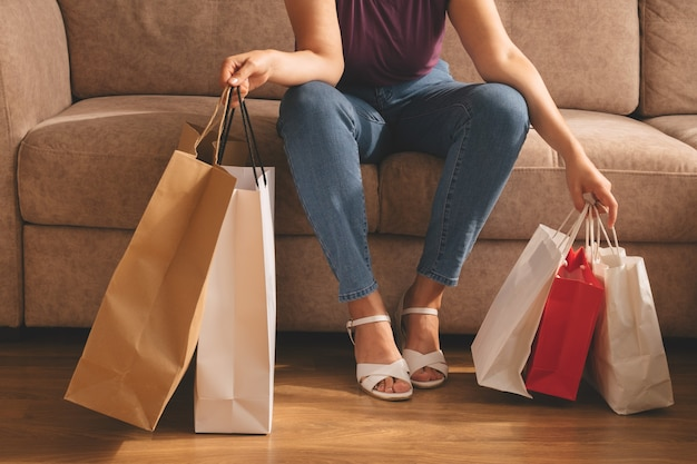 Jonge stijlvolle vrouw met boodschappentassen en zittend op een bank