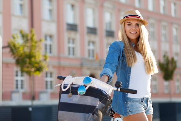 Jonge stijlvolle vrouw met een fiets