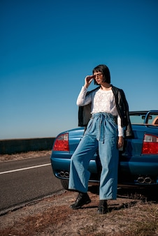 Jonge stijlvolle vrouw met een kapsel dat in de buurt van een auto zonder dak staat