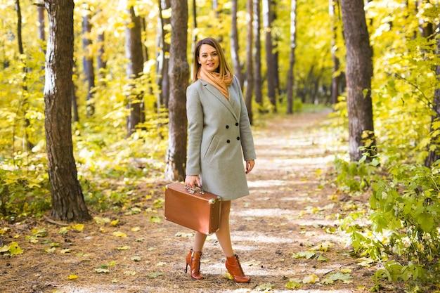 Jonge stijlvolle vrouw met retro koffer wandelen in herfst park