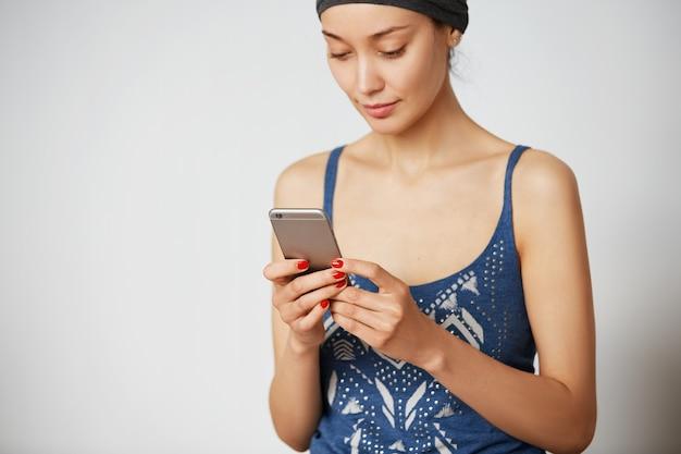 Jonge stijlvolle vrouw online nieuws lezen zittend tegen een witte lege muur