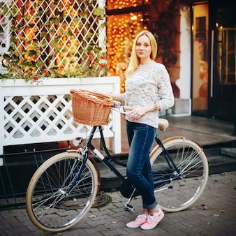 Jonge stijlvolle vrouw op een vintage fiets