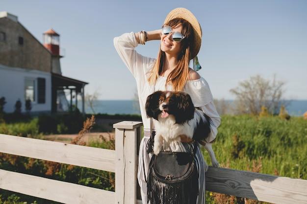Jonge stijlvolle vrouw op het platteland, met een hond, blij positieve stemming, zomer, strooien hoed, outfit in bohemien stijl, zonnebril, glimlachen, blij, zonnig