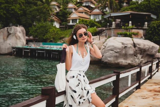 Jonge stijlvolle vrouw permanent op pier, wandelen, luisteren naar muziek op koptelefoon, zomerkleding, witte rok, handtas, azuurblauw water, landschapsachtergrond, tropische lagune, vakantie, reizen in azië