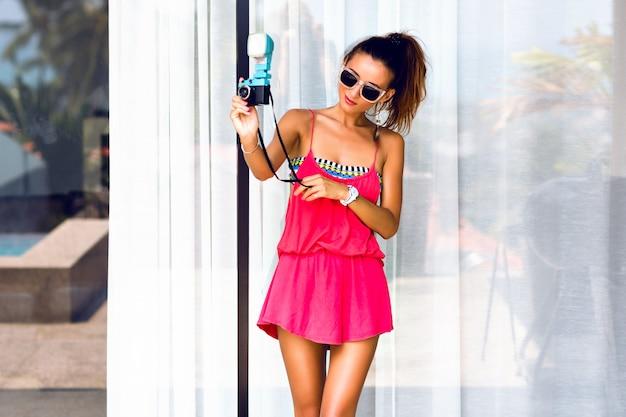 Jonge stijlvolle vrouw selfie maken op trendy vintage camera, poseren glimlachend en plezier maken.