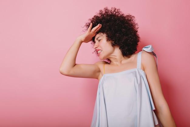 Jonge stijlvolle vrouw wendde zich bang af en sloot haar ogen en houdt haar hand tegen haar hoofd op roze