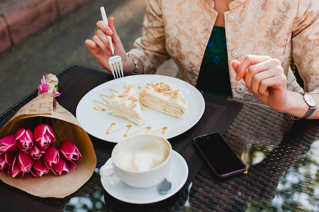 Jonge stijlvolle vrouw zitten in café, kopje cappuccino houden en lekkere taart eten,