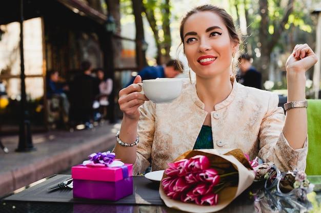 Jonge stijlvolle vrouw zitten in café, kopje cappuccino te houden