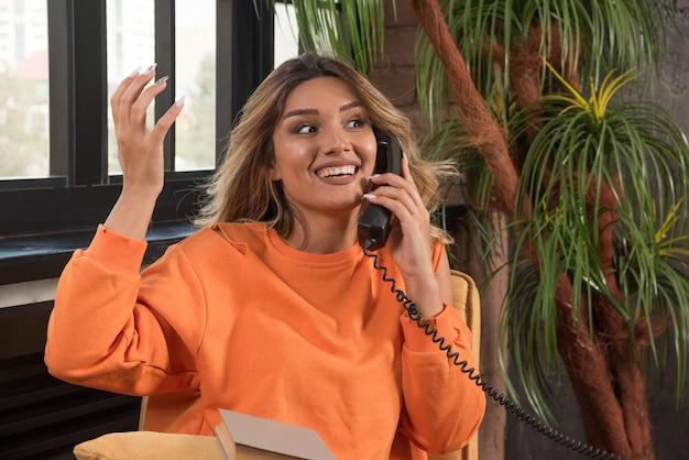 Jonge stijlvolle vrouw zitten in fauteuil praten met telefoon terwijl haar hand wordt weergegeven.
