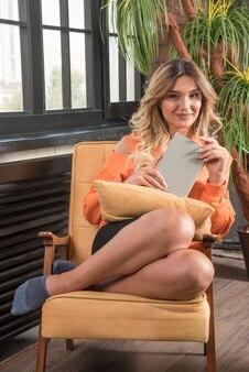 Jonge stijlvolle vrouw zittend in een leunstoel boek houden terwijl glimlachen.
