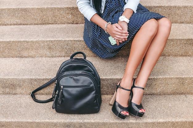 Jonge stijlvolle vrouw zittend op de trap met smartphone, luisteren naar muziek op koptelefoon, rugzak, glimlachen, gelukkig, positieve stemming, zomervakantie, vintage denim stijl
