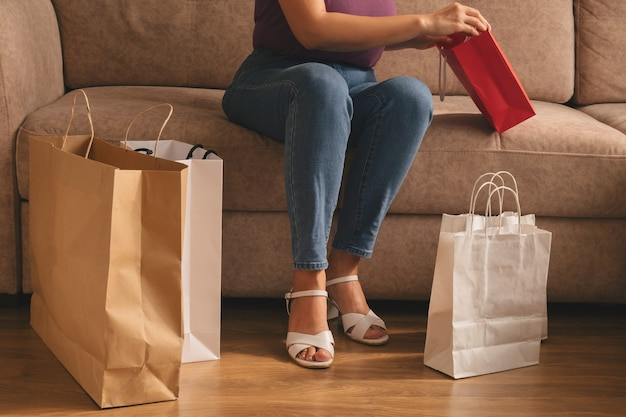 Jonge stijlvolle vrouw zittend op een bank met boodschappentassen