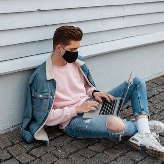 Jonge stijlvolle zakenman in spijkerbroek verdedigt zichzelf tegen het covid-19-virus met medisch zwart masker en werkt op afstand op een laptop buitenshuis. aardige freelancer in quarantaine. stijl 2020.