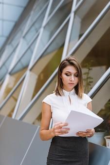 Jonge stijlvolle zakenvrouw lezen van documenten