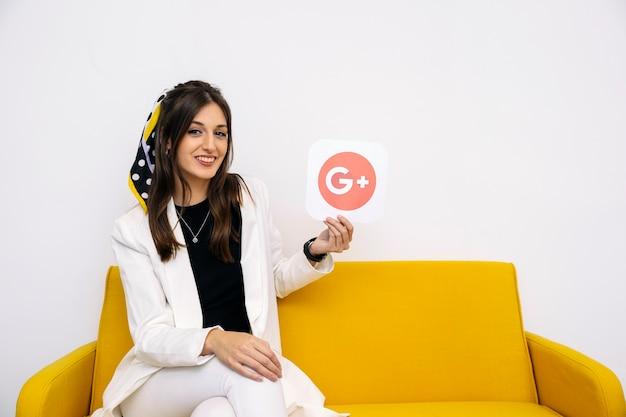 Jonge stijlvolle zakenvrouw weergegeven: google plus pictogram in haar hand