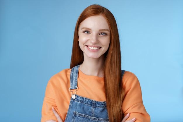 Jonge stijlvolle zelfverzekerde glimlachende vrouwelijke roodharige freelancer verzekerd werk gedaan groot grijnzend tevreden handen vasthouden gekruist borst zelfverzekerd staande blauwe achtergrond goed humeur vrolijke houding