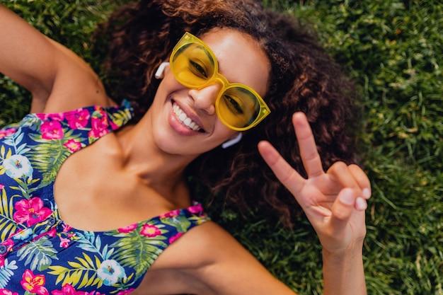 Jonge stijlvolle zwarte vrouw luisteren naar muziek op draadloze oortelefoons met plezier in park, zomer fashion stijl, kleurrijke hipster outfit, liggend op het gras, van bovenaf bekijken